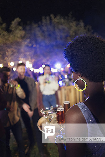 Young woman serving cocktails at garden party