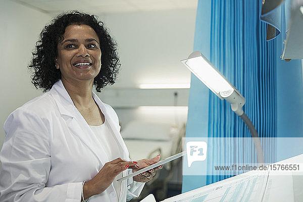 Smiling female doctor using digital tablet in hospital room Smiling female doctor using digital tablet in hospital room