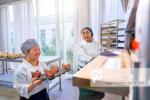 Koch und junge Frau mit Down-Syndrom schieben Muffins in den Ofen