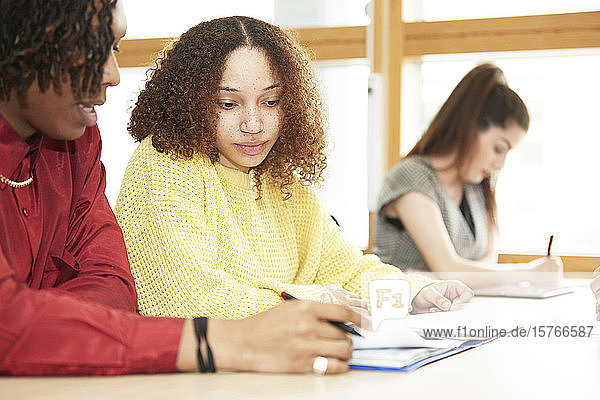 Focused college students studying together in classroom