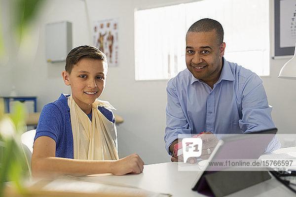 Portrait male doctor prescribing medication to boy in doctors office