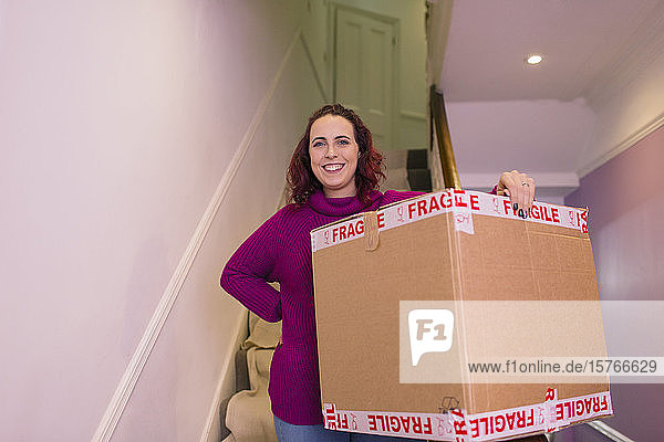 Portrait confident woman moving into new home  carrying cardboard box Portrait confident woman moving into new home, carrying cardboard box