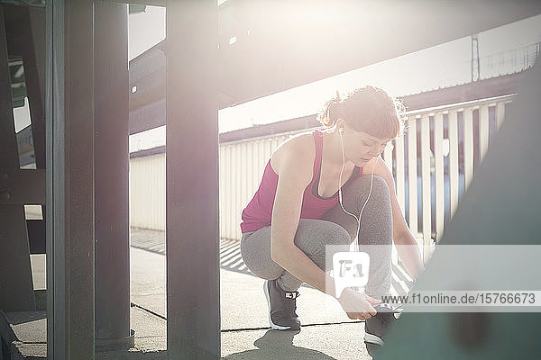 Young female runner tying shoe on sunny urban sidewalk
