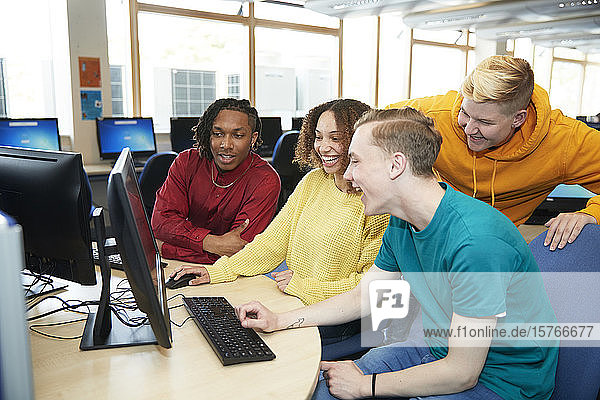 Happy young college students using computer together in library