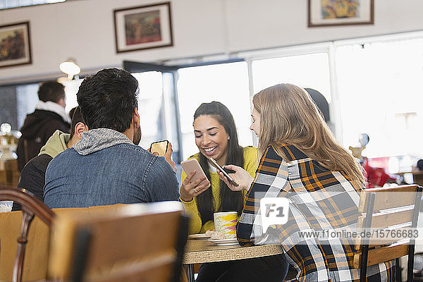 Young adult friends using smart phones in cafe