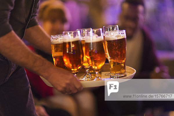 Man serving tray of beers to friends Man serving tray of beers to friends