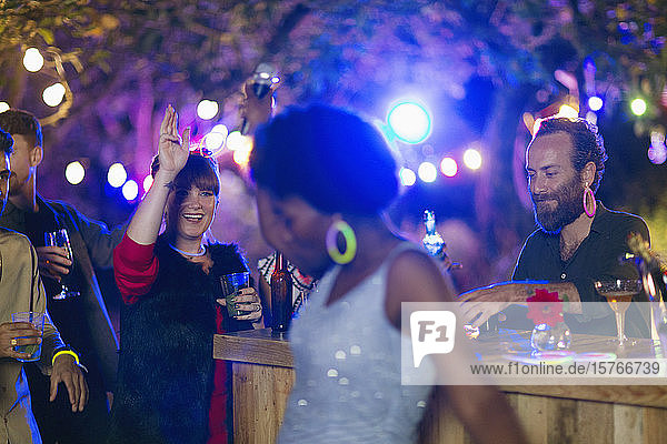 Friends dancing and drinking at garden party