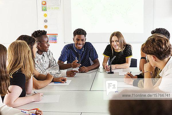 Smiling high school students talking in debate class Smiling high school students talking in debate class