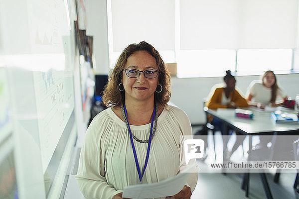 Porträt einer selbstbewussten Gymnasiallehrerin vor einer Projektionsfläche im Klassenzimmer