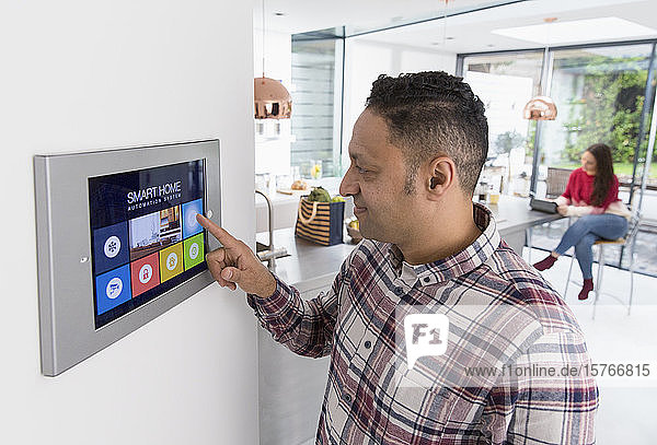 Man setting touch screen smart home alarm