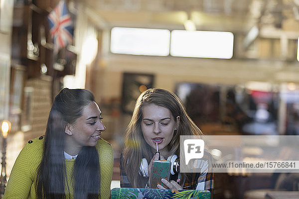 Young women applying lip gloss in cafe window