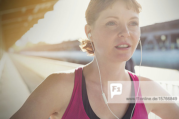 Close up confident young female runner with headphones