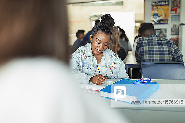 High school girl student doing homework at table in classroom