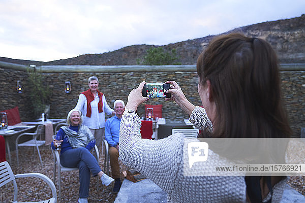 Woman with camera phone photographing senior friends on hotel patio
