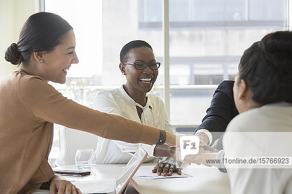 Happy business people joining hands in conference room meeting Happy business people joining hands in conference room meeting
