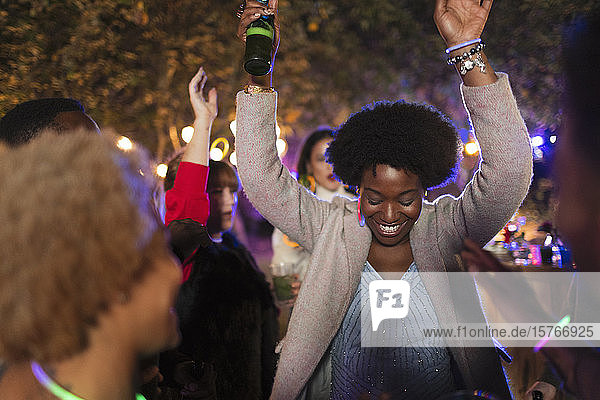 Carefree woman dancing and drinking at garden party Carefree woman dancing and drinking at garden party