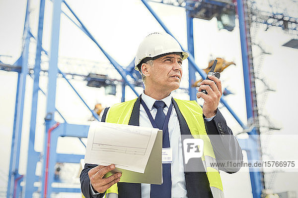 Dock manager with walkie-talkie and clipboard at shipyard