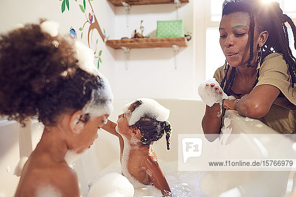 Mother giving daughters bubble bath Mother giving daughters bubble bath