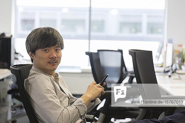 Portrait confident businessman with smart phone in office Portrait confident businessman with smart phone in office