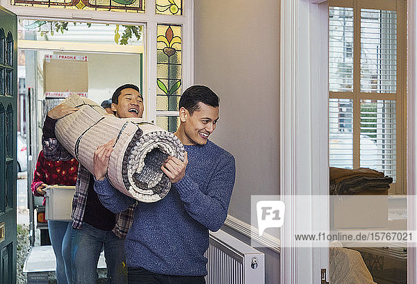 Men moving house  carrying rug in corridor
