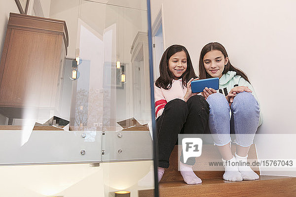 Sisters using smart phone on stairs at home