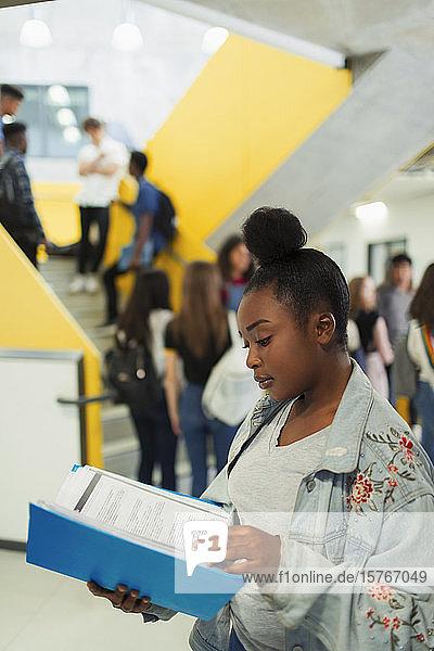 Junior high girl student studying in corridor Junior high girl student studying in corridor