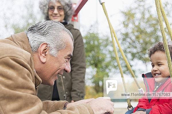 Großvater spielt mit seinem Enkel auf einer Schaukel auf dem Spielplatz