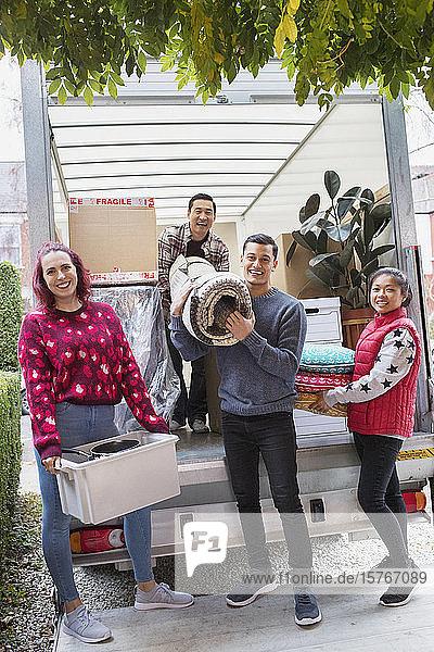 Portrait happy friends unloading belongings from moving van