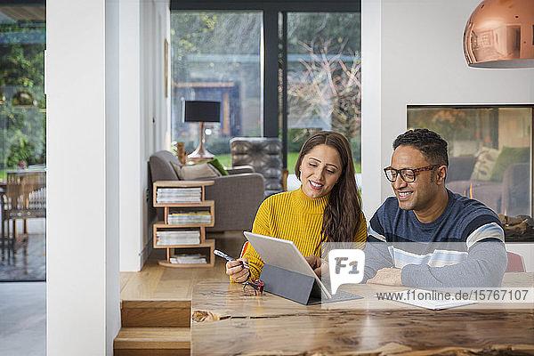 Ehepaar bezahlt Rechnungen am digitalen Tablet am Esstisch