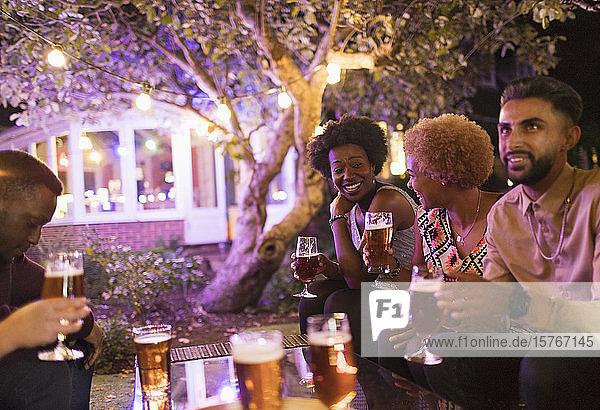 Freunde unterhalten sich und trinken Bier bei einer Gartenparty