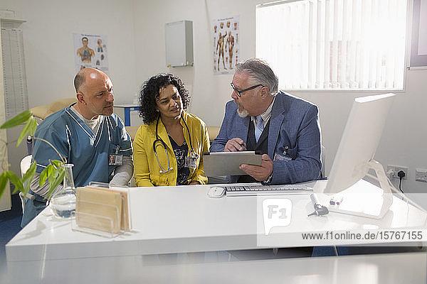 Ärzte und Verwaltungsangestellte mit digitalem Tablet  Besprechung in einer Arztpraxis