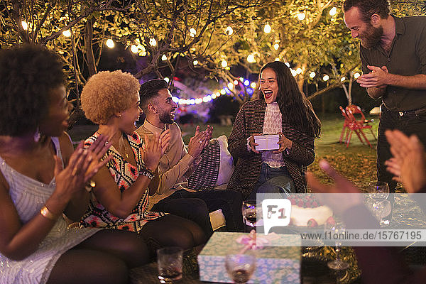 Friends surprising woman with gift at garden birthday party