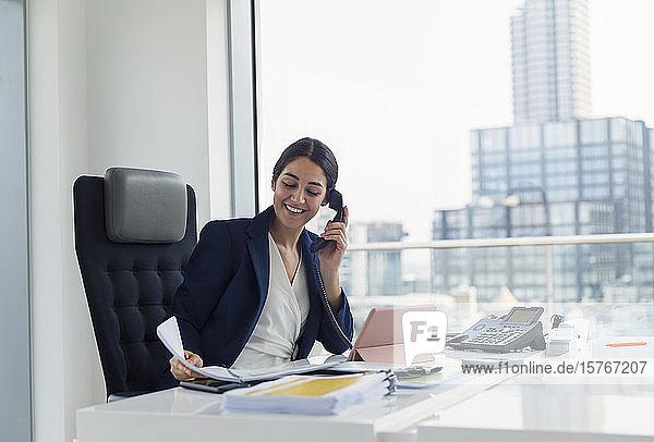 Lächelnde Geschäftsfrau im Gespräch am Telefon in einem städtischen Büro