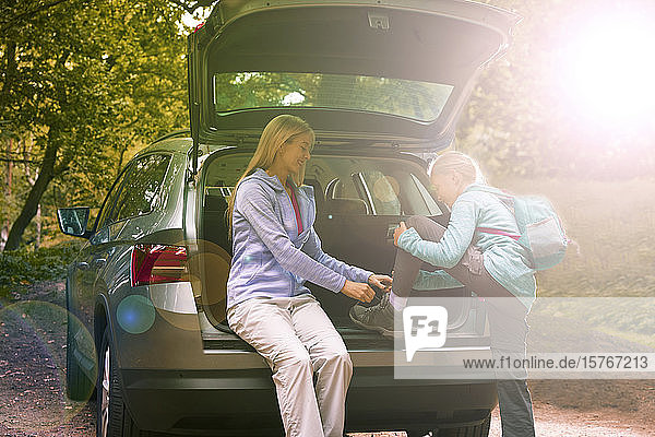 Mother helping daughter tie hiking boots at back of sunny car