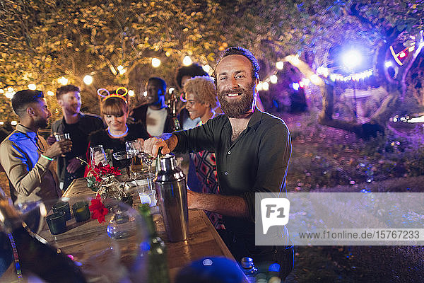 Portrait happy man bartending for friends at garden party