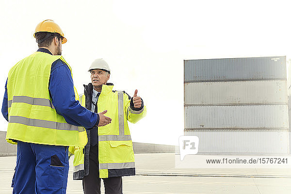 Dock worker and manager talking at shipyard