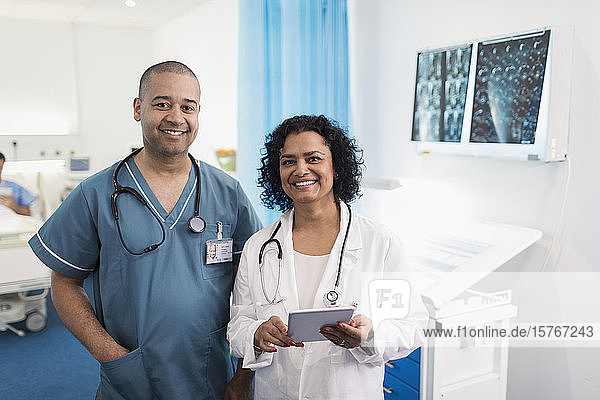 Portrait confident doctors with digital tablet in hospital room