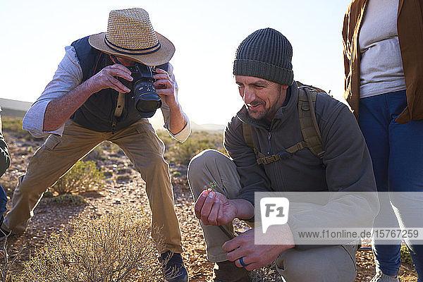 Safari tour guide explaining plants to tourist with camera Safari tour guide explaining plants to tourist with camera