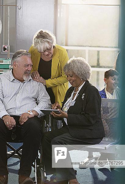 Arzt mit digitalem Tablet im Gespräch mit einem Paar in der Kliniklobby