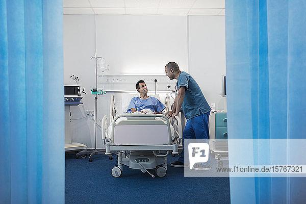 Krankenpfleger im Gespräch mit einem Patienten  der sich im Krankenhauszimmer ausruht
