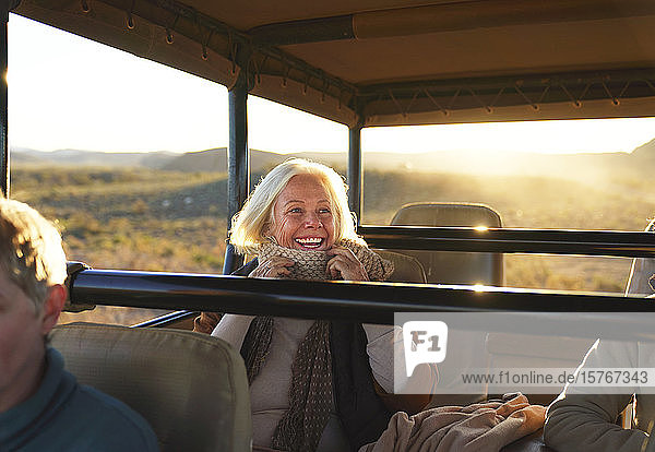 Happy senior woman on safari riding in off-road vehicle