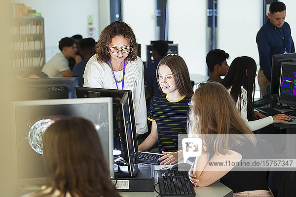 Female junior high teacher helping girl student at computer in computer lab