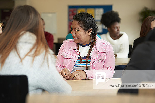 Young female college student listening to classmate in classroom