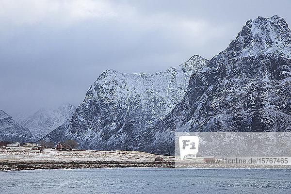 Snow covered mountains above village Flakstadpollen Lofoten Norway