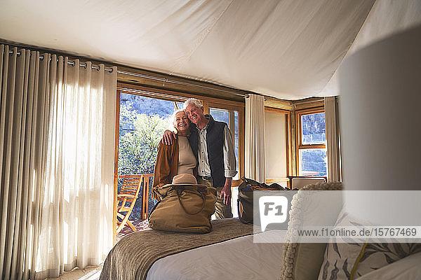 Portrait happy senior couple hugging in hotel bedroom Portrait happy senior couple hugging in hotel bedroom
