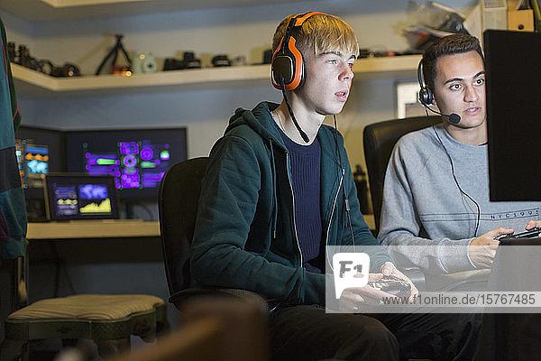Teenager-Jungen mit Kopfhörern spielen ein Videospiel am Computer in einem dunklen Raum