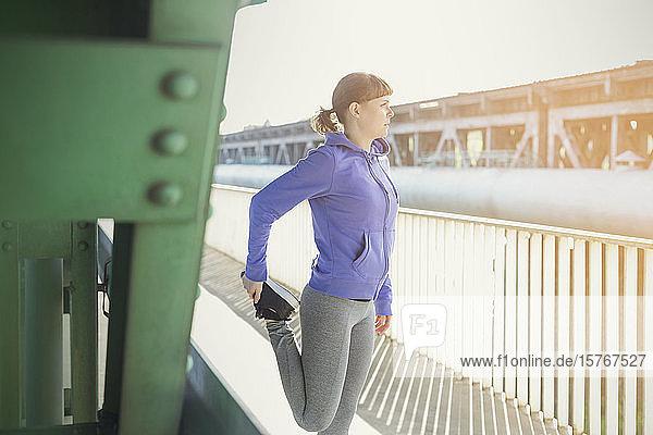 Young female runner stretching leg along sunny urban railing