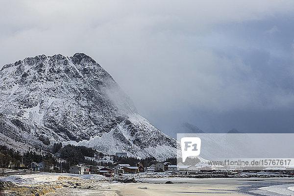 Snow covered mountain above remote village Ramberg Lofoten Norway