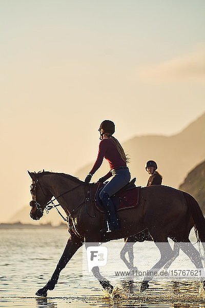 Young woman horseback riding on ocean beach at sunset