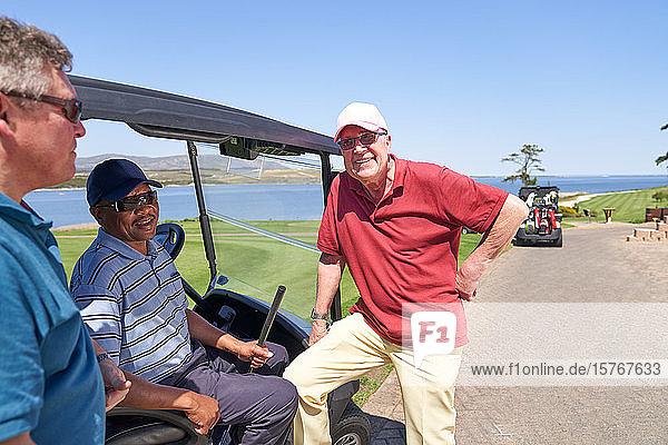 Happy male golfer friends talking at golf cart on sunny course
